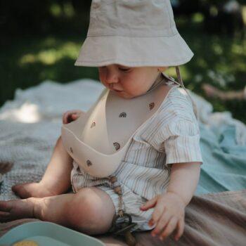 Bebé con babero silicona con arcoíris