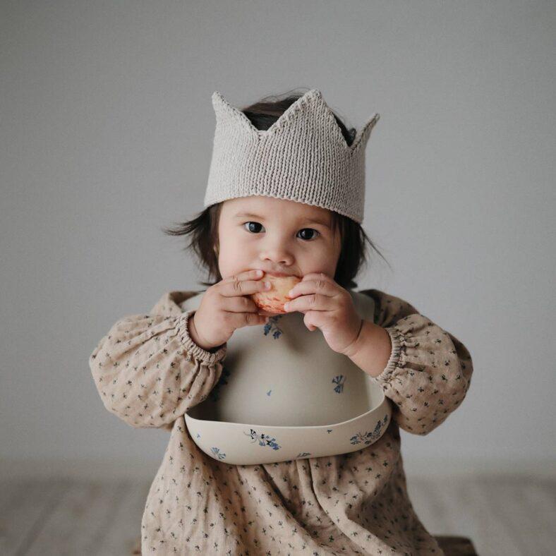 Bebé con babero de silicona con lilas