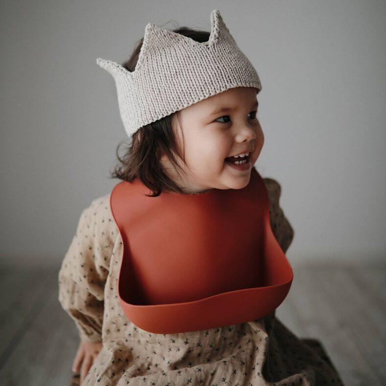 Bebé con babero de silicona rojo