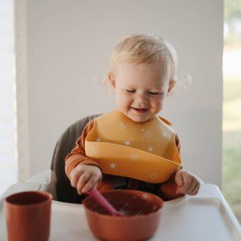 Bebé con babero silicona con soles