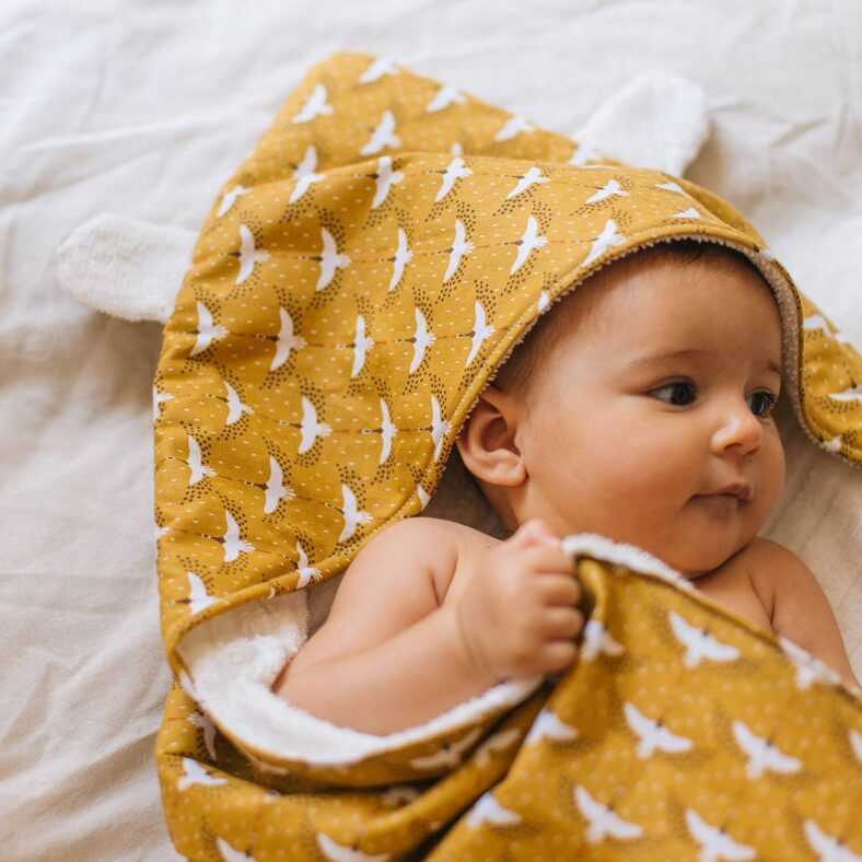 Bebé con capa de baño grullas