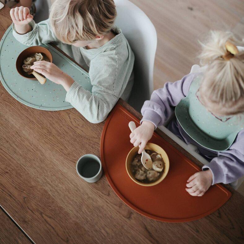 Niños comiendo con manteles individuales de silicona de Mushie