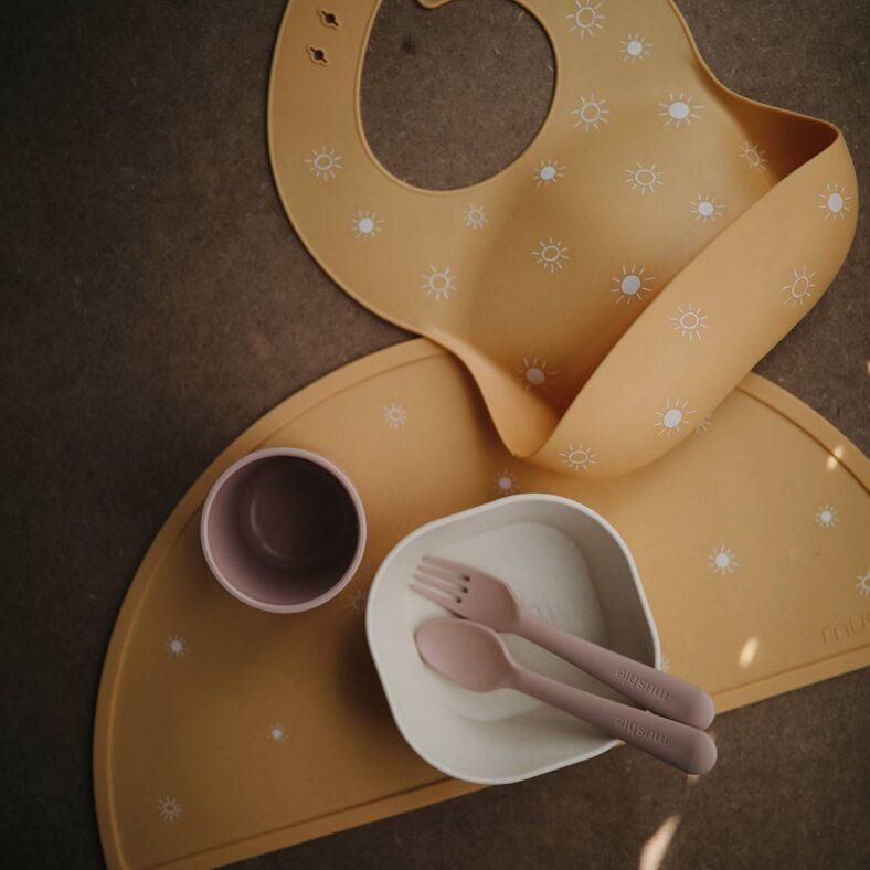 Mantel de silicona Mushie con soles
