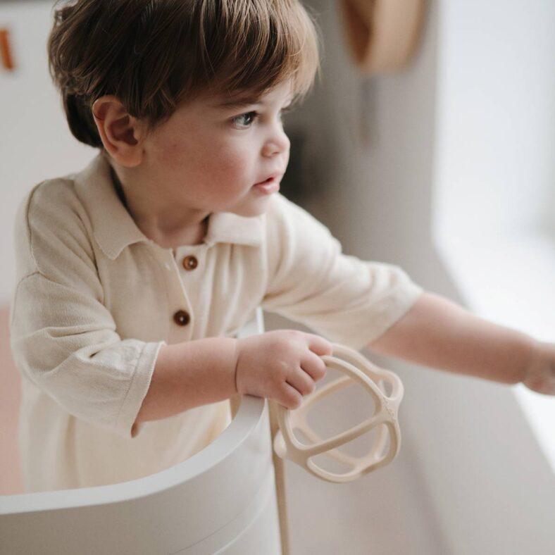 Niño jugando con mordedor de silicona geométrico marfil