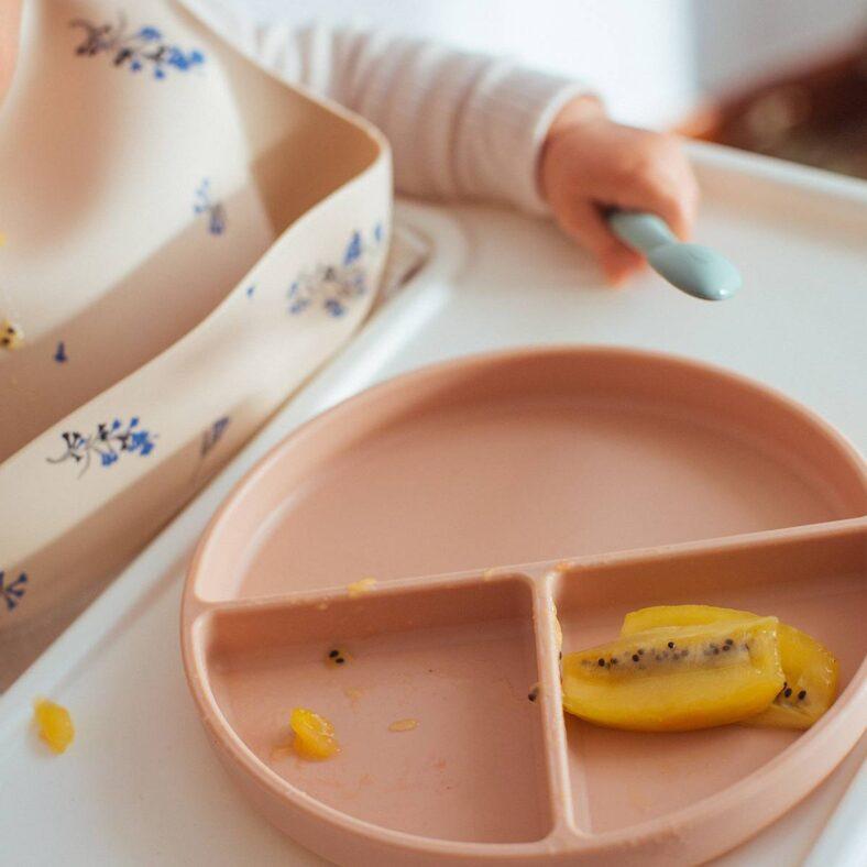 Plato de silicona rosa de Mushie con bebé comiendo