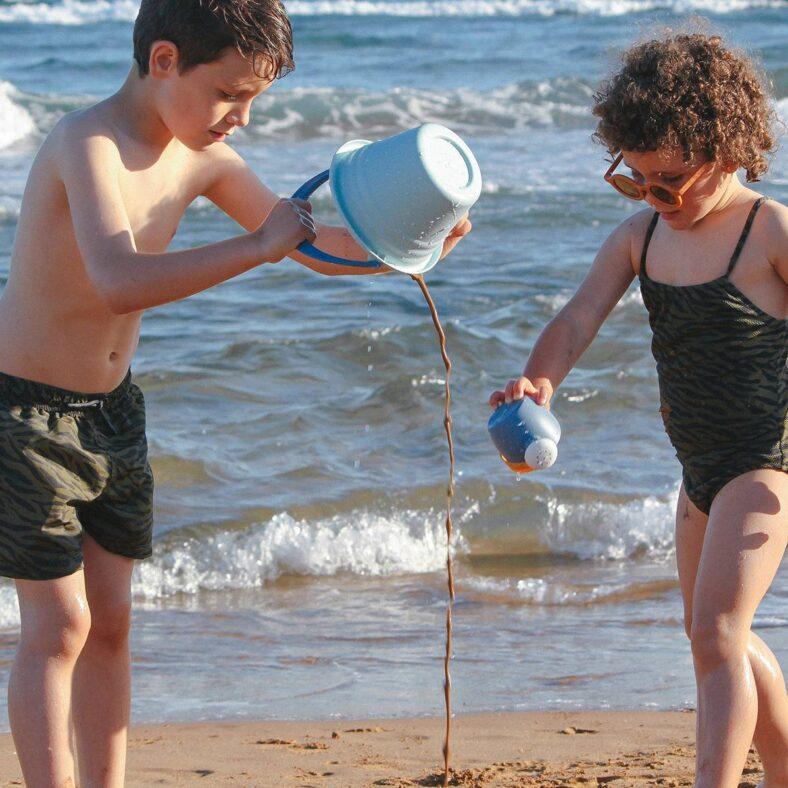 Niños jugando con el set de playa de juguetes biodegradables