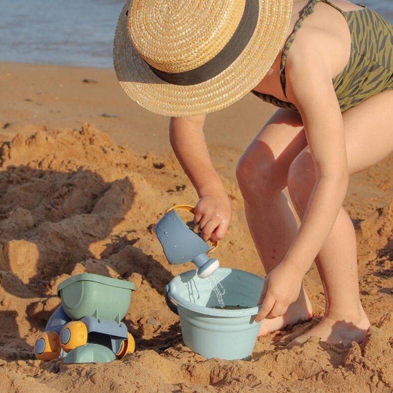 Niña jugando con el set de playa de juguetes biodegradables