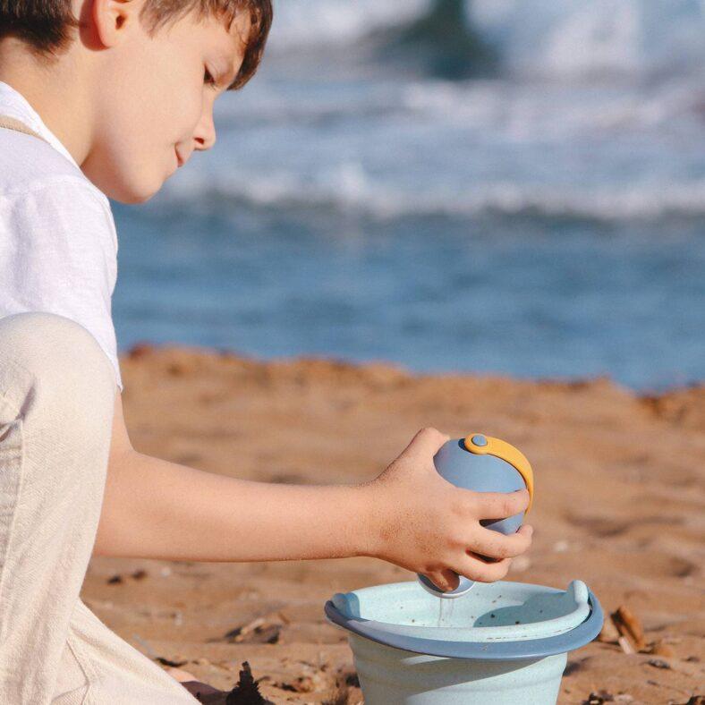 Niño jugando con el set de playa de juguetes biodegradables