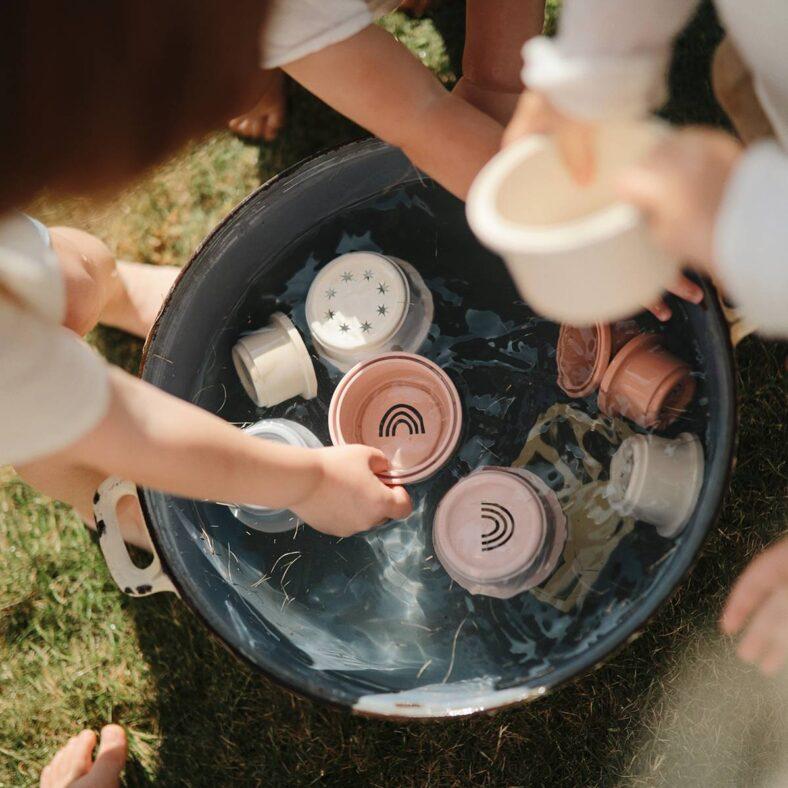 niños jugando con vasitos apilables agua original pastel