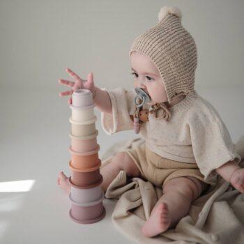 niña jugando con vasitos apilables petal