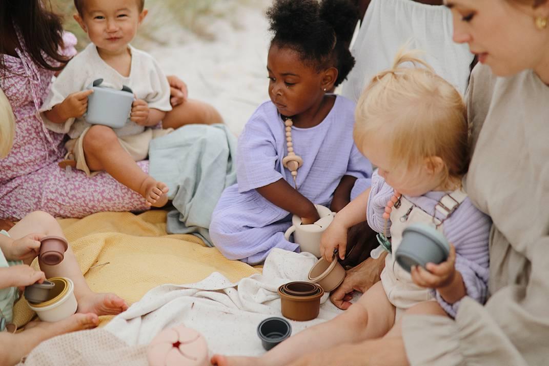 niños con vasitos apilables mushie